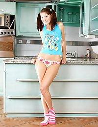 A teenage hottie in a kitchen caressing her young pussy